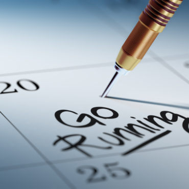 Concept image of a Calendar with a golden dart stick. The words Go running written on a white notebook to remind you an important appointment.